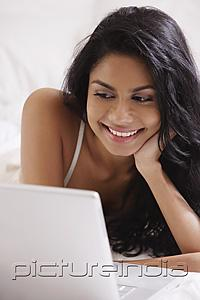 PictureIndia - Close up of Indian woman looking at laptop computer