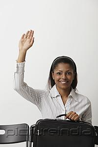 PictureIndia - Young woman raises her hand and smiles