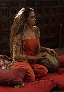 PictureIndia - Young woman relaxing on pillows with Indian antiques