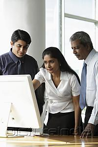 PictureIndia - Indian woman looking at a computer with male colleagues