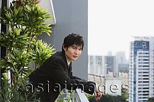 Asia Images Group - young man in suit at balcony