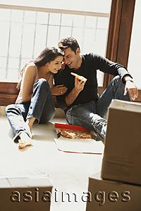 Asia Images Group - young couple having pizza on floor