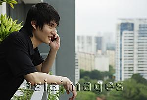 Asia Images Group - young man standing at balcony, using mobile phone