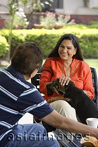 Asia Images Group - couple sitting outdoors, playing with dog