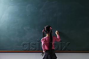 AsiaPix - rear view of young girl writing on chalkboard