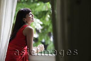 Asia Images Group - Indian woman looking out window, smiling
