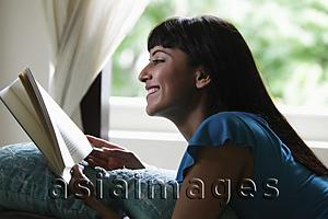 Asia Images Group - Young woman laying on stomach reading a book and smiling