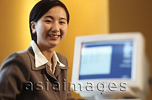 Asia Images Group - Female executive sitting at desk with computer, portrait, yellow background