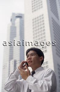 Asia Images Group - Male executive talking on cellular phone with office buildings behind, low angle view