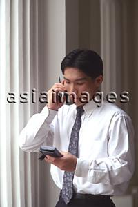 Asia Images Group - Male executive talking on cellular phone, pillars behind
