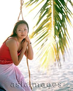 Asia Images Group - Woman sitting on swing looking off camera, coconut frond in background