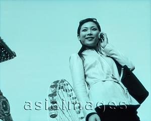 Asia Images Group - Woman on cellular phone, ferris wheel in background.
