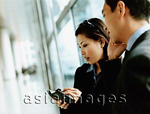 Asia Images Group - Executives using PDA and cellular phone.