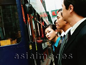 Asia Images Group - Executives waiting for bus, female executive looking at camera.