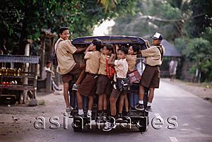 Asia Images Group - Indonesia, Lombok, Schoolboys riding on the back of a van.