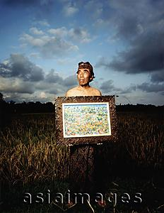 Asia Images Group - Indonesia, Bali, Ubud, Balinese artist holding painting in rice field.