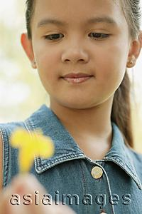 Asia Images Group - Young girl holding a flower