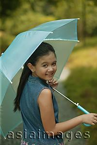 Asia Images Group - Young girl holding an umbrella, looking over shoulder