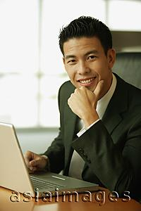 Asia Images Group - Young man with hand on chin, looking at camera, toothy smile