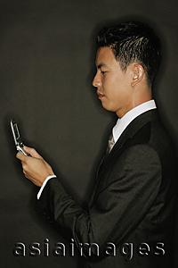 Asia Images Group - Young man using mobile phone, text messaging