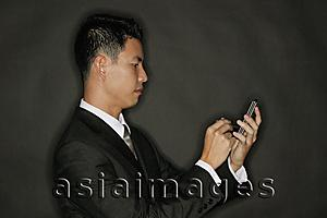 Asia Images Group - Young man using PDA, standing in profile