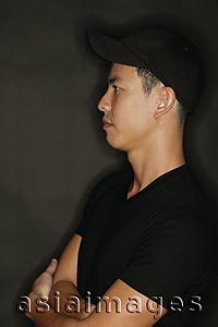 Asia Images Group - Young man with arms crossed, black background