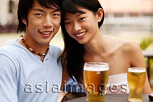 Asia Images Group - Couple sitting at cafe, cheek to cheek, looking at camera