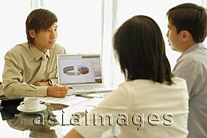 Asia Images Group - Young man showing laptop to couple in front of him