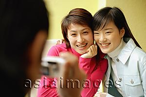 Asia Images Group - Young man holding camera, two women posing for picture