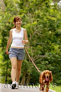 Asia Images Group - Young woman walking her dog