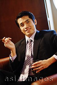 Asia Images Group - Young businessman holding cigar and glass of whiskey, looking away