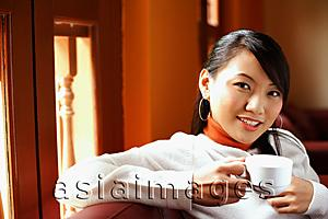 Asia Images Group - Young woman holding cup, looking at camera
