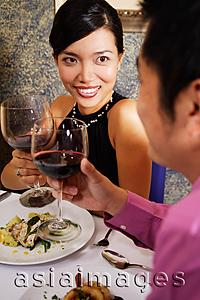 Asia Images Group - Couple in restaurant holding wine glasses for a toast