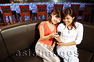 Asia Images Group - Two women sitting side by side, looking at mobile phone