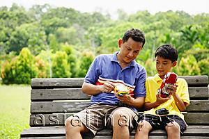 Asia Images Group - Father and son, sitting on bench, holding remote control cars
