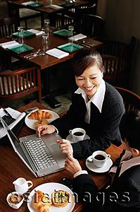 Asia Images Group - Two businesswomen at cafe with laptop