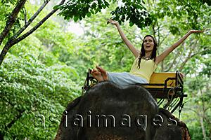 Asia Images Group - Female tourist riding elephant, arms outstretched, Phuket, Thailand