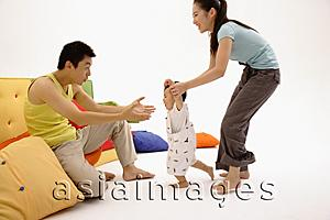 Asia Images Group - Father sitting on sofa, arms outstretched, toddler walking towards him, guided by the mother