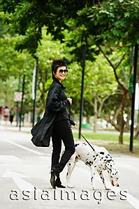 Asia Images Group - Woman dressed in black, walking dog