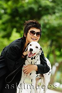 Asia Images Group - Woman with sunglasses embracing Dalmatian