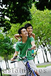 Asia Images Group - Young couple on tandem bicycle, smiling at camera