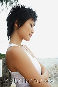 Asia Images Group - Woman in sleeveless top, eyes closed, arms crossed