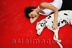 Asia Images Group - Woman lying down with Dalmatian on red blanket