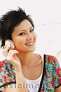 Asia Images Group - Woman holding shell to ear, looking at camera, smiling
