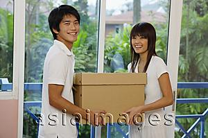 Asia Images Group - Couple carrying a box, looking at camera