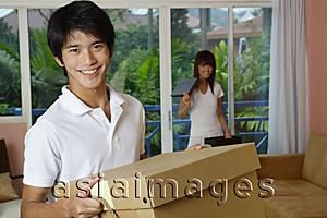 Asia Images Group - Man carrying a box, smiling at camera, woman in the background