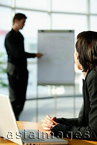 Asia Images Group - Female executive sitting at desk, turning to look at colleague standing next to flip board