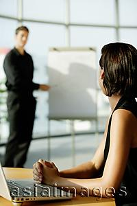 Asia Images Group - Female executive sitting at desk, looking at colleague standing next to flip board