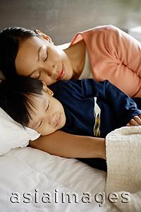 Asia Images Group - Mother and son sleeping on bed