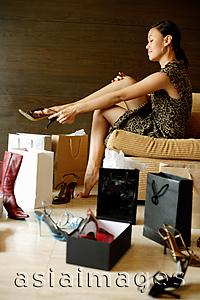 Asia Images Group - Woman putting on high heel shoes, surrounded by shopping bags, shoes boxes and shoes